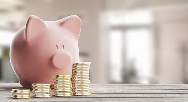 在硬币后面的小猪存钱罐高清图片